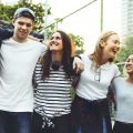 Smiling happy young adult friends arms around shoulder outdoors